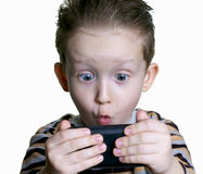O menino foi surpreendido olhar no telefone Foto de Stock Royalty Free