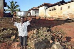 O menino ganês leva a escala com água em sua cabeça Fotos de Stock Royalty Free