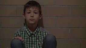 O menino golpeado só triste senta-se no assoalho que lokking na câmera, ninguém está esperando o menino em casa fotografia de stock royalty free