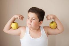 O menino gordo no t-shirt mostra os músculos com as maçãs em seus bíceps Foto de Stock