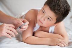 O menino gordo pequeno olha as mãos dos doutores com uma seringa Imagem de Stock Royalty Free