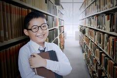 O menino guarda o livro no corredor da biblioteca Imagens de Stock