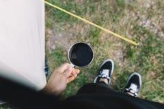 O menino guarda uma caneca de café com café preto em sua mão Fotografia de Stock