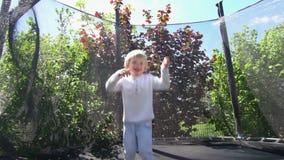 O menino impertinente da criança salta no trampolim com rede protetora Movimento lento 100fps filme