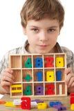 O menino indica figuras de madeira no formulário dos numerais Foto de Stock Royalty Free