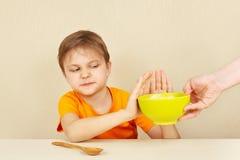 O menino infeliz pequeno recusa comer o papa de aveia Fotografia de Stock Royalty Free