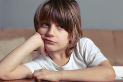 O menino infeliz senta-se na mesa Foto de Stock Royalty Free