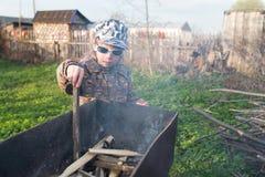 O menino inflama um fogo na grade foto de stock
