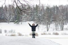 O menino inspirado feliz aumenta as mãos na paisagem da natureza da neve Wh do homem Foto de Stock