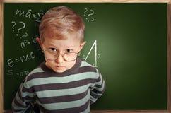 O menino inteligente do aluno nos monóculos aproxima o schoolboard Fotografia de Stock Royalty Free