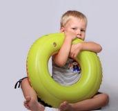 O menino joga com um anel de borracha para a natação Fotos de Stock Royalty Free