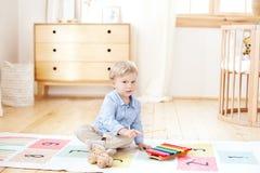 O menino joga em um jardim de inf?ncia no xilofone menino que joga com o xilofone do instrumento musical do brinquedo na sala de  imagem de stock