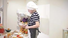 O menino joga na cozinha das crianças video estoque