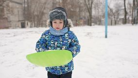 O menino joga a neve na câmera no fundo do inverno video estoque