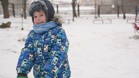 O menino joga a neve na câmera no fundo do inverno vídeos de arquivo