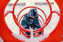 O menino joga no campo de jogos no tonnel no inverno fotografia de stock