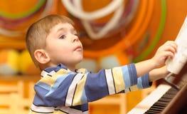 O menino joga o piano Imagens de Stock