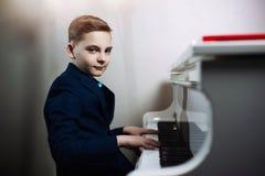 O menino joga o piano A criança à moda aprende jogar um instrumento musical imagem de stock royalty free