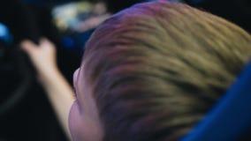 O menino joga um simulador do carro no salão dos slots machines Close-up de sua cara Está sentando-se no assento de piloto filme