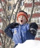 O menino joga um snowball. Imagens de Stock Royalty Free