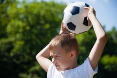 O menino joga uma bola Fotos de Stock Royalty Free