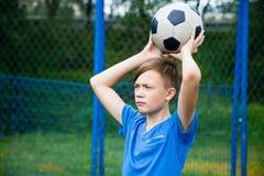 O menino joga uma bola para fora Imagens de Stock Royalty Free