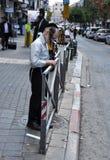 O menino judaico está colando o anúncio no Jerusalém foto de stock