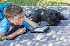 O menino lê fora Fotos de Stock Royalty Free