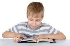 O menino lê o livro Fotografia de Stock Royalty Free