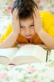 O menino lê um livro na cama Fotos de Stock Royalty Free