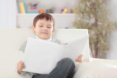 O menino lê um livro no sofá no berçário Foto com espaço da cópia imagem de stock