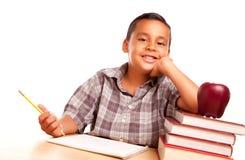 O menino latino-americano adorável com livros, Apple, escreve fotografia de stock