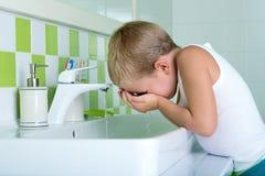 O menino lava a cara no banheiro O começo de um dia novo imagem de stock royalty free