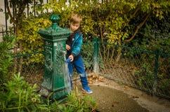 O menino lava seu brinquedo em uma fonte de água decorativa em Paris Imagens de Stock Royalty Free