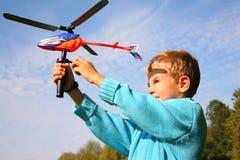 O menino liga o helicóptero do brinquedo Fotografia de Stock Royalty Free