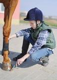 O menino limpa um casco do cavalo Fotografia de Stock Royalty Free