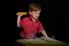O menino louro amassa a massa manchada com a farinha foto de stock