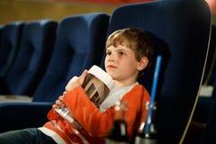 O menino louro bonito da criança que come a pipoca no cinema antes do filme começa Criança feliz que tem o divertimento e que esp fotos de stock