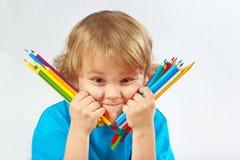 O menino louro bonito novo prende lápis da cor fotos de stock royalty free