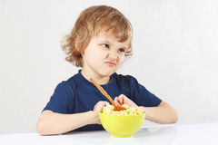 O menino louro bonito pequeno recusa comer o papa de aveia Fotos de Stock Royalty Free