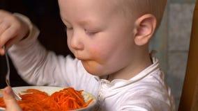 O menino louro engraçado está comendo a salada coreana da cenoura na cozinha ao lado de seu irmão As crian?as est?o felizes junto vídeos de arquivo