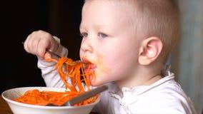 O menino louro engraçado está comendo a salada coreana da cenoura na cozinha ao lado de seu irmão As crian?as est?o felizes junto video estoque