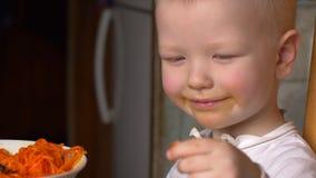O menino louro engraçado está comendo a salada coreana da cenoura na cozinha ao lado de seu irmão As crian?as est?o felizes junto filme
