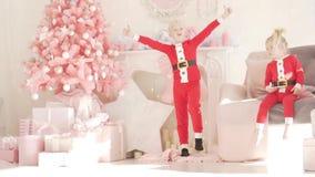 O menino louro está dançando na árvore do ano novo vídeos de arquivo