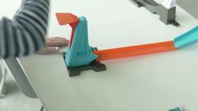 O menino louro lança o carro do brinquedo na trilha video estoque
