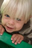 O menino louro novo adere-se à escada de etapa Imagens de Stock