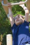 O menino louro novo está jogando em barras de macaco. Imagens de Stock Royalty Free
