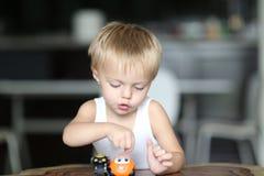 O menino louro pequeno bonito está jogando com um carro pequeno do brinquedo em casa imagens de stock