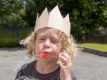 O menino louro pequeno faz bolhas foto de stock