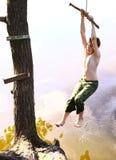 O menino mante-se distraído com balanço da água em férias Foto de Stock